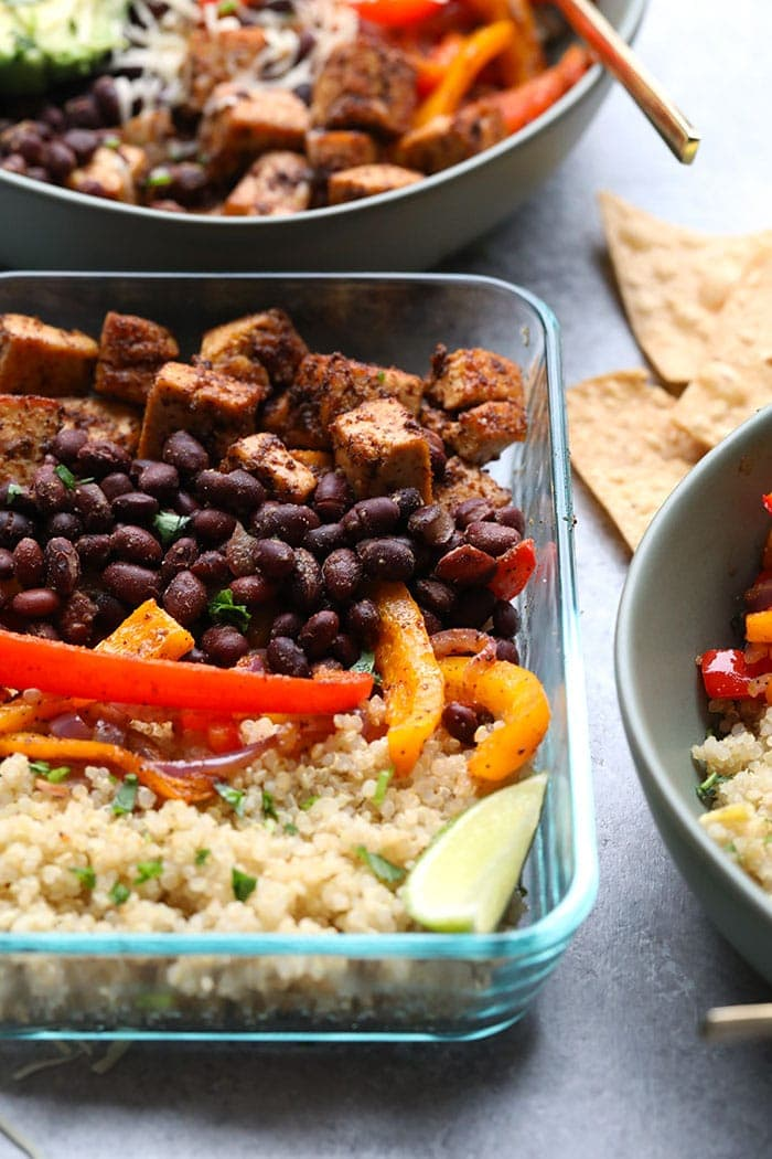 Meal prep sheet pan tofu quinoa burrito bowls in a meal prep glass container.