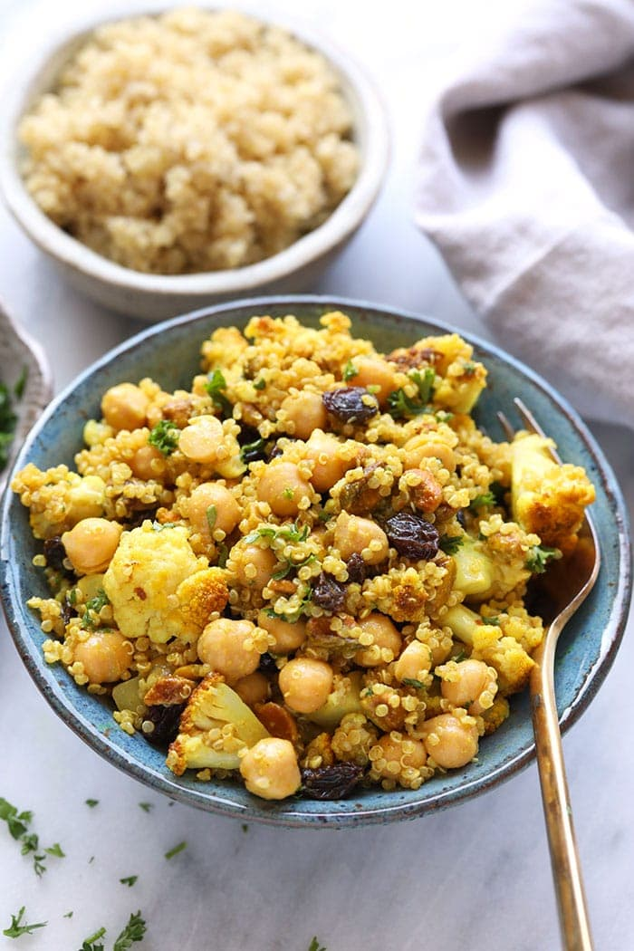 Golden roasted cauliflower quinoa salad in a bowl with a fork