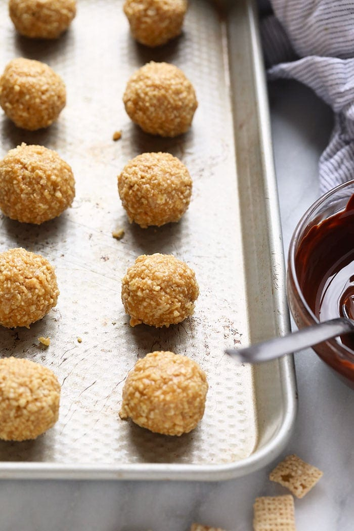 Crunchy no bake peanut butter balls after being rolled out on a baking sheet