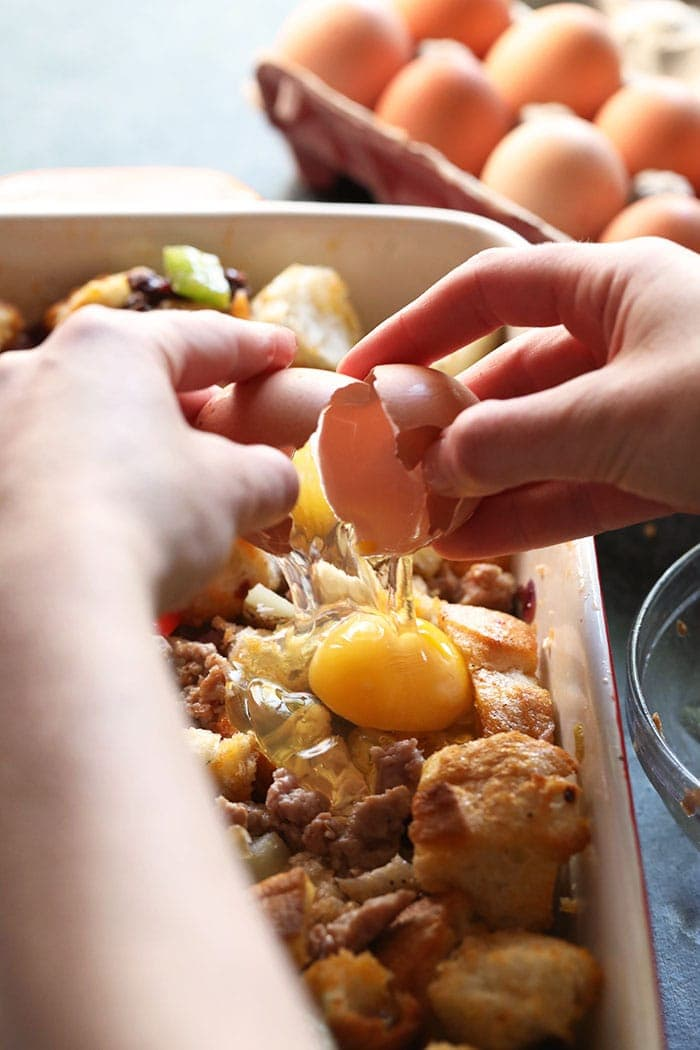 two hands cracking an egg onto casserole mixture