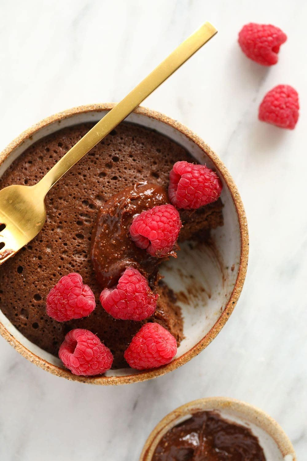 single-serve chocolate mug cake with a bite taken out of it and topped with delicious fresh raspberries