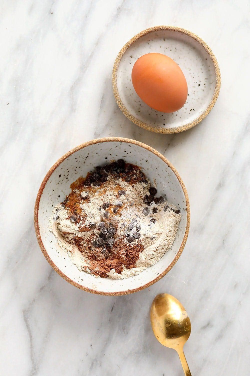 chocolate mug cake dry ingredients in a bowl with an egg ready to be cracked into the mix