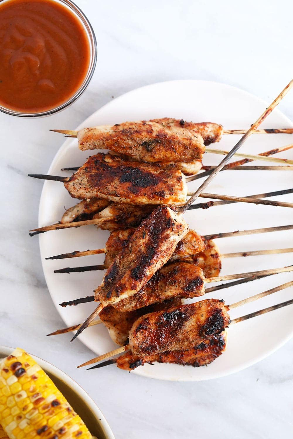 Grilled skewers on plate next to bbq sauce and grilled corn.