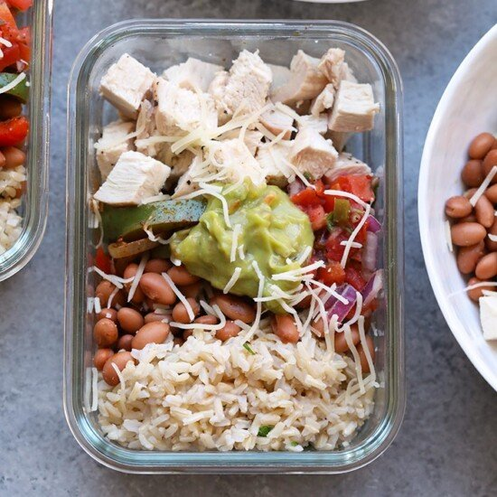 Save your money and make your own affordable Copycat Chipotle Chicken Burrito Bowls at home! These healthy chicken burrito bowls are made just like the real thing made with baked chicken, cilantro lime brown rice, beans, and fajita veggies, and your favorite toppings!