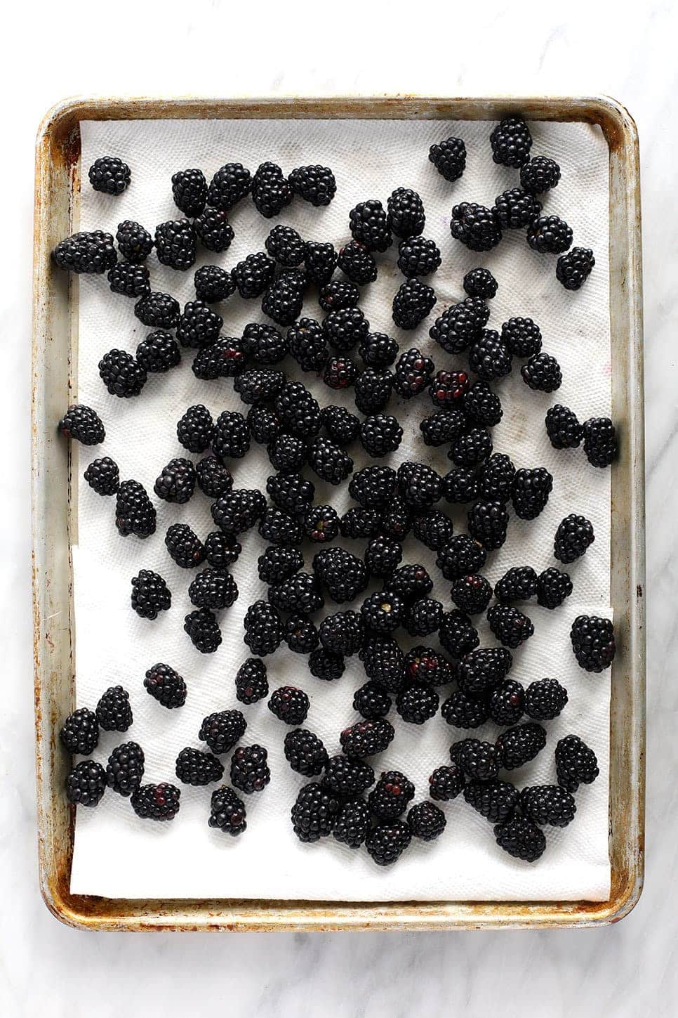 blackberries on a baking sheet and paper towel drying