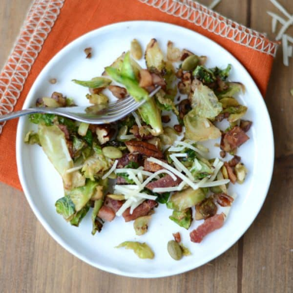 brussel sprout salad with bacon with parmesan cheese on white plate with fork