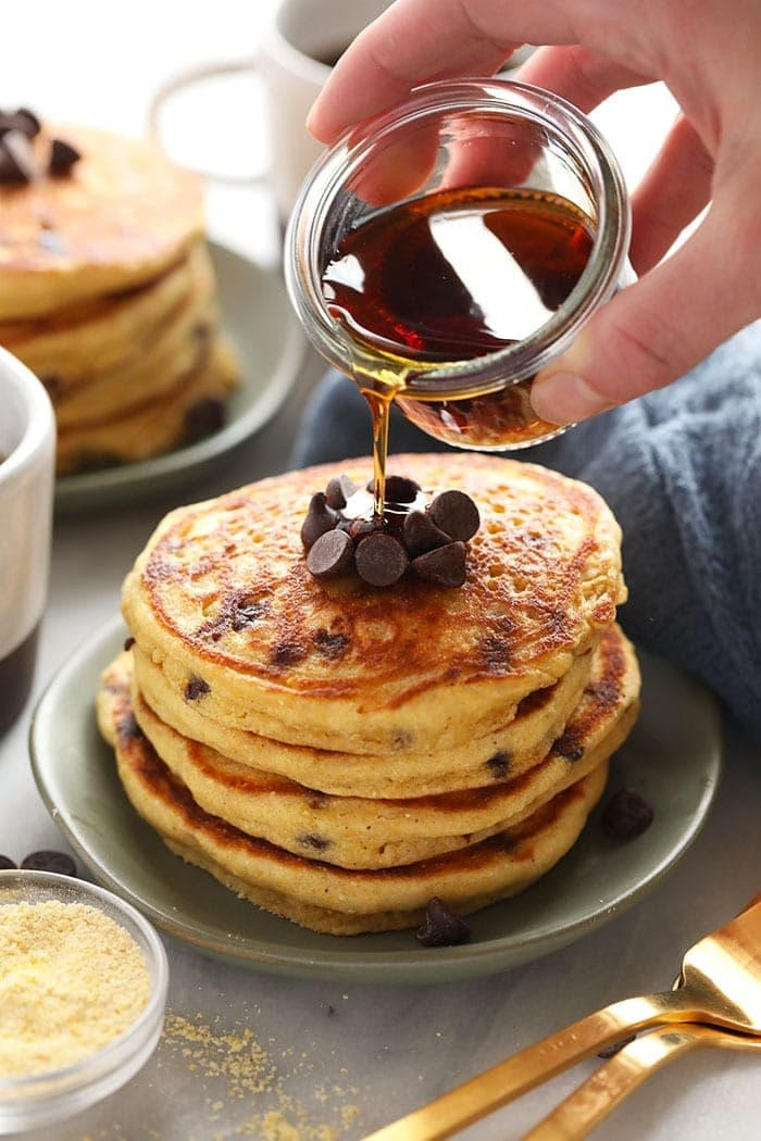 pouring maple syrup onto pancakes
