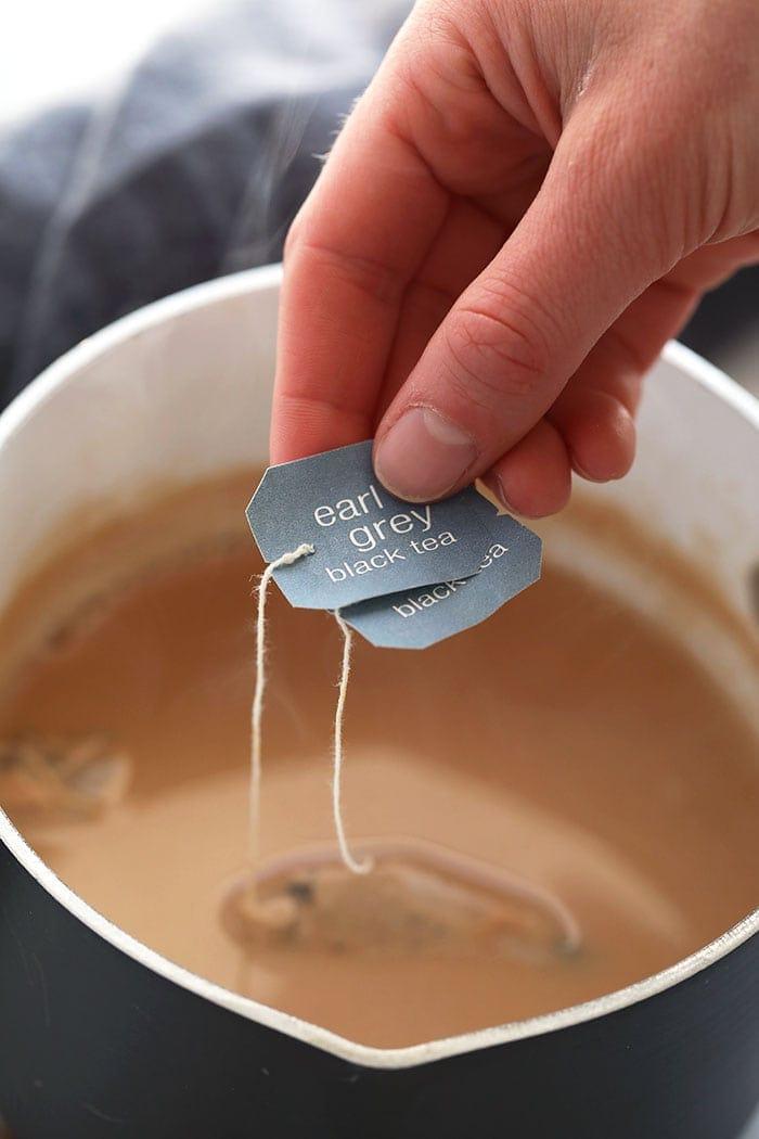 seeping earl grey black tea in a pot of almond milk
