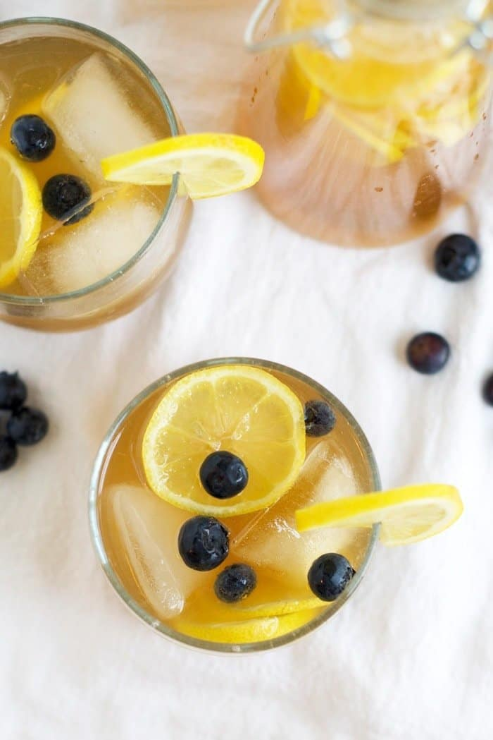 Kombucha Lemonade in two cups with lemons and blueberries