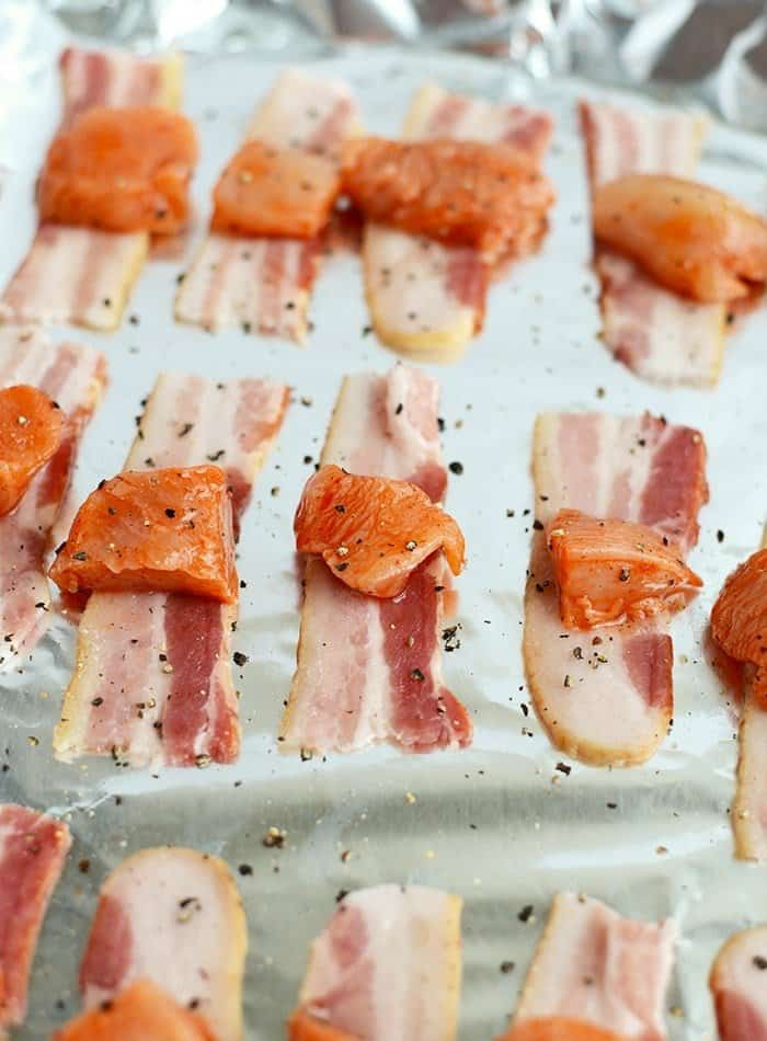 Serve these Bacon-Wrapped Honey Sriracha Chicken Bites on a piece of apple for the most delicious, paleo-friendly appetizer that only takes 30 minutes to make!