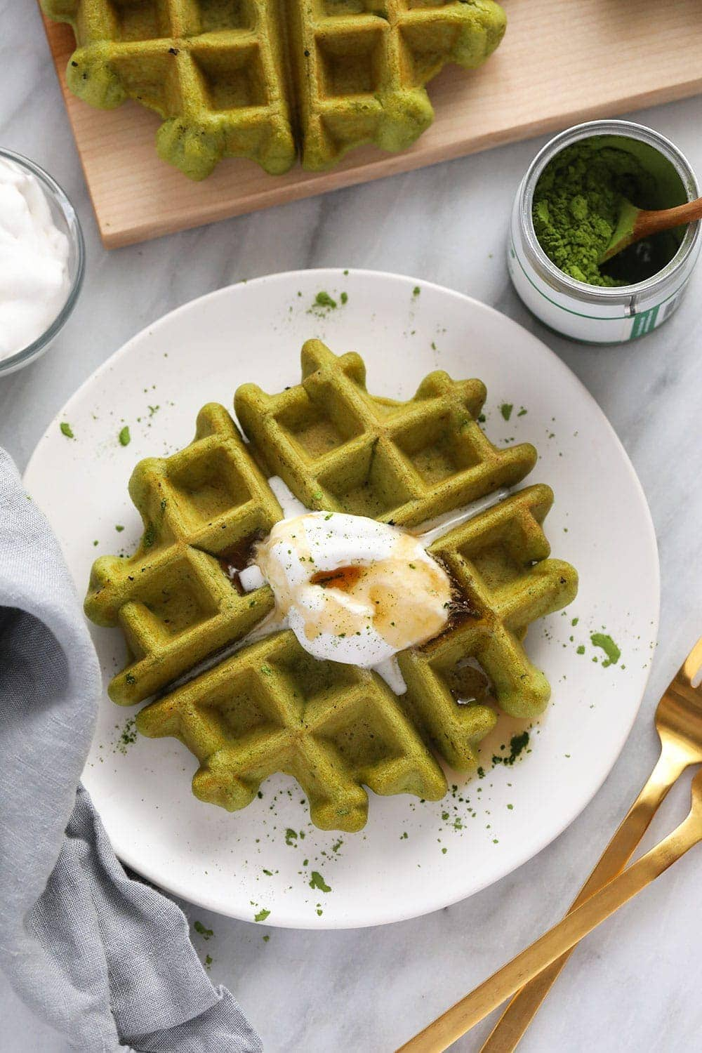 matcha waffle on plate with coconut whipped cream