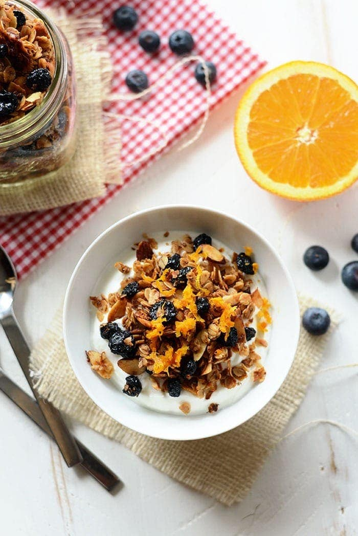 blueberry orange granola in a bowl with milk