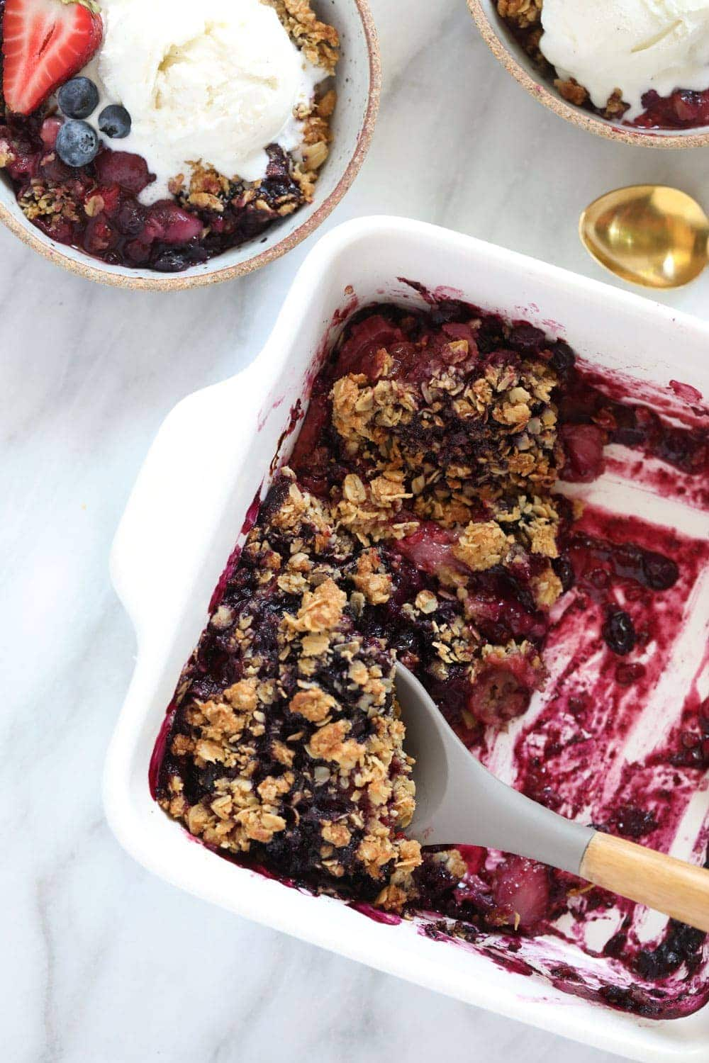 berry crumble in a white dish with serving spoon