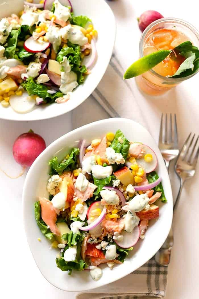 greek yogurt dill dressing over salmon salad in white bowls