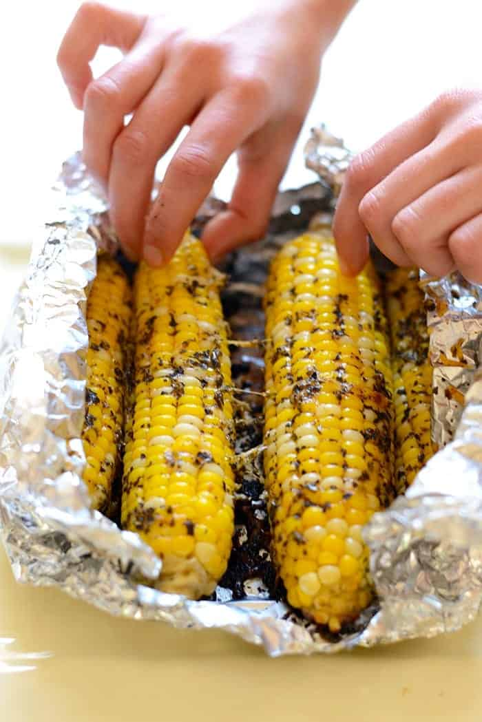 Grilled corn on the cob in tin foil after being cooked.