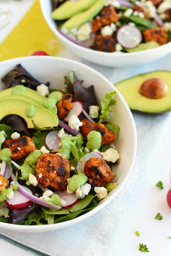 This Sriracha Chicken Salad is packed with veggies and blue cheese. It's topped with a homemade green goddess dressing that's made with a Greek yogurt base!