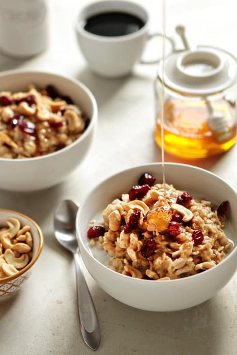 Cozy up with delicious, homemade oatmeal with cashew butter, cashews, cranberries and honey.