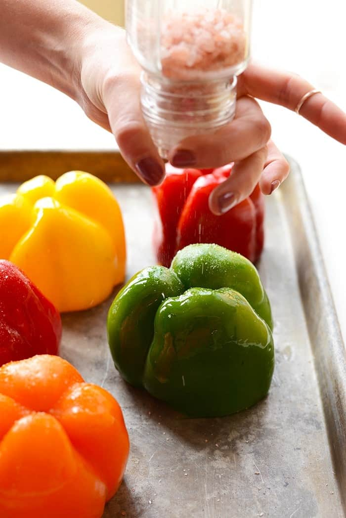 colorful bell peppers upside down being sprinkled with salt for mexican stuffed peppers