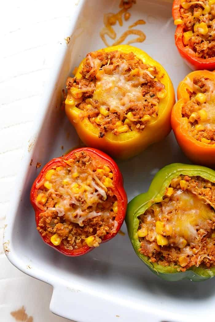 dish full of colorful Mexican stuffed peppers with melted cheese