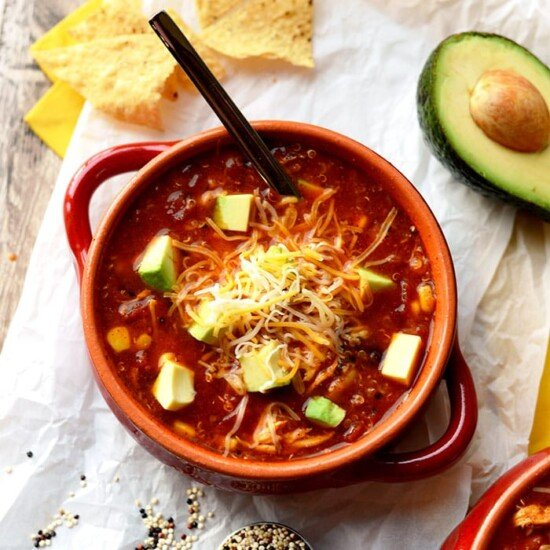chicken enchilada soup in a bowl topped with avocado and shredded cheese
