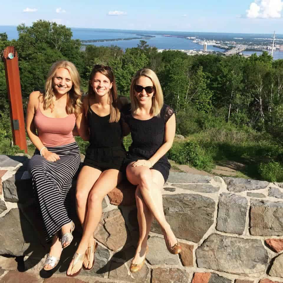 3 women sitting on rock wall