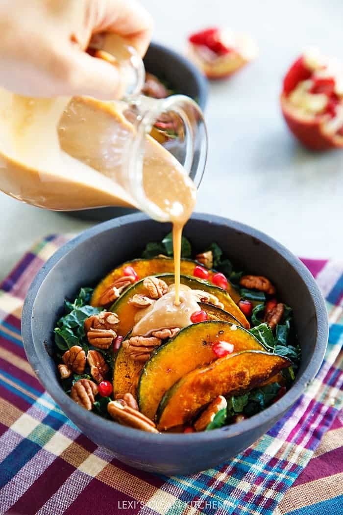 This Salad has all the ingredients you'll want in a Fall dish! Packed with chopped kale, roasted squash, pomegranate seeds, toasted pecans and topped with a super easy & delicious Maple Balsamic for the absolute perfect Thanksgiving salad!