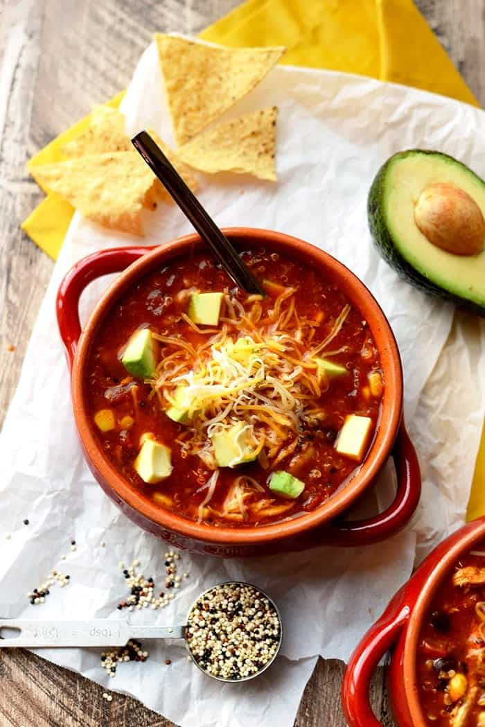 chicken enchilada soup in a bowl with sliced avocado