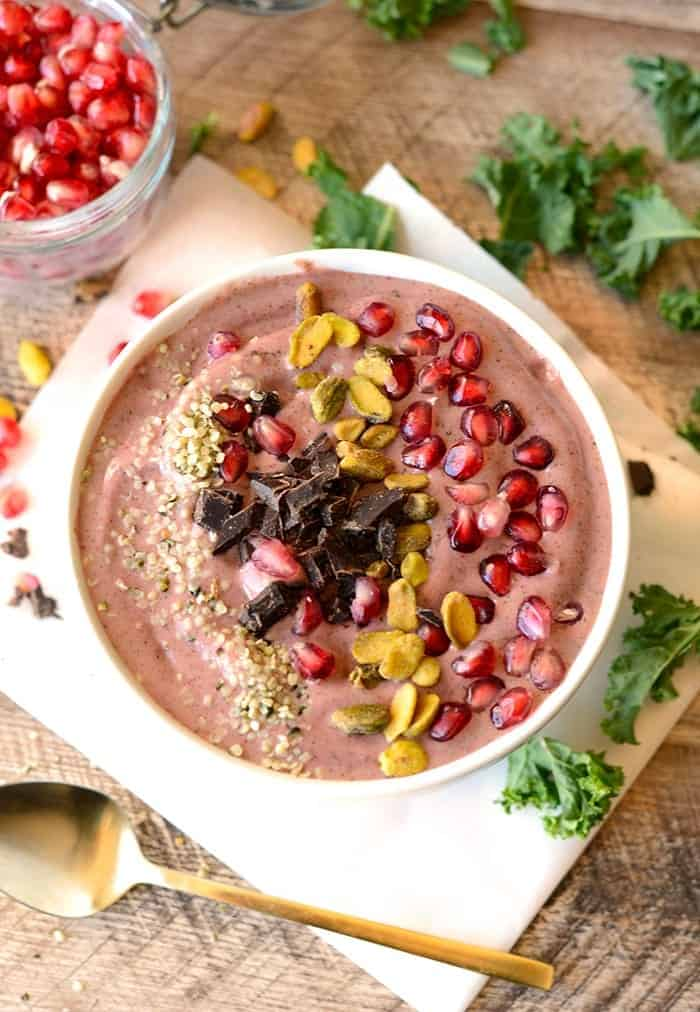 Get fancy with your smoothie and make this delicious pomegranate green smoothie bowl topped with pomegranate arils, pistachios, hemp seeds, and dark chocolate!