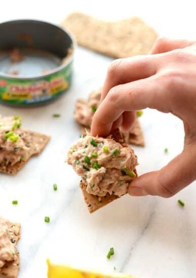 Hand holding Healthy Tuna Salad on cracker next to empty can of tuna