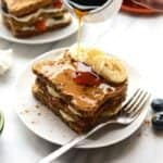 Stuffed french toast on a plate with maple syrup and banana slices