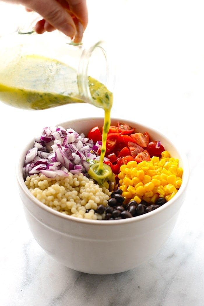 lime dressing being poured over black bean couscous salad in bowl