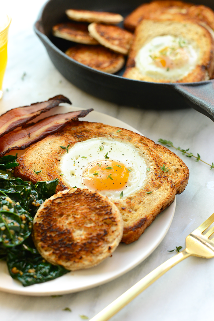 egg in a hole on plate with bacon