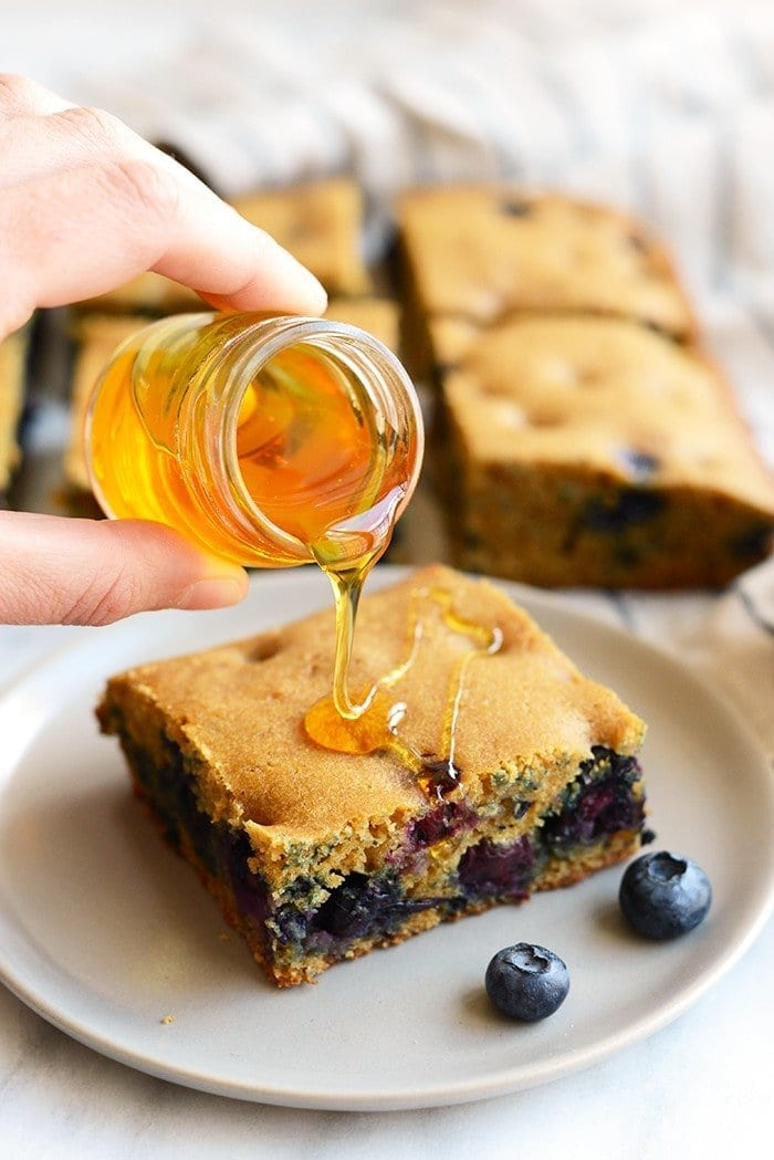 Pouring honey over blueberry breakfast cake