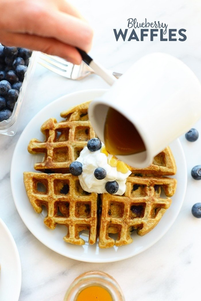 Syrup being poured on a blueberry waffle