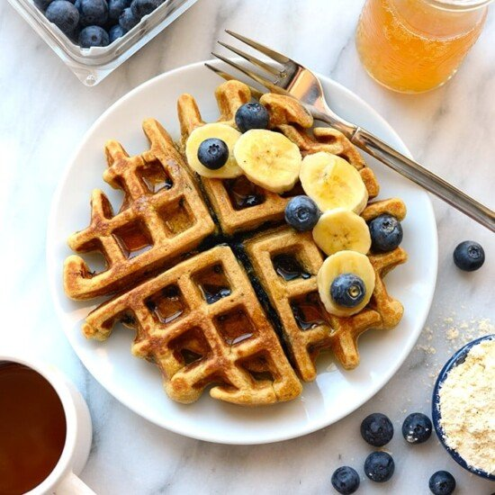 Healthy blueberry waffle with banana slices on white plate