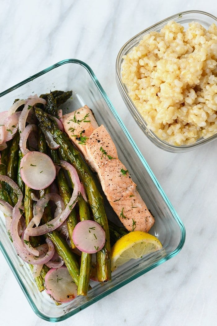 cooking salmon in a pan with lemon butter with side of rice