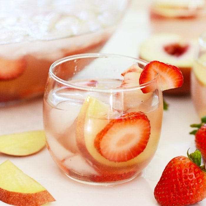 strawberry peach rose sangria in a stemless wine glass ready to be enjoyed
