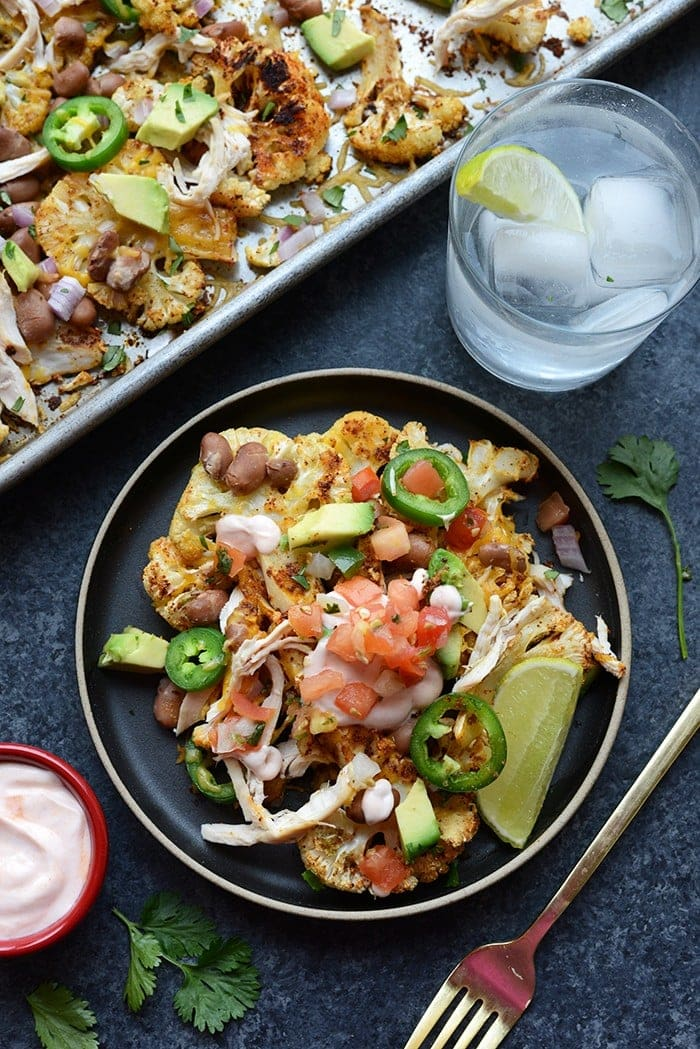 cauliflower nachos topped with pulses, rotisserie chicken, pico de gallo, and avocado on plate