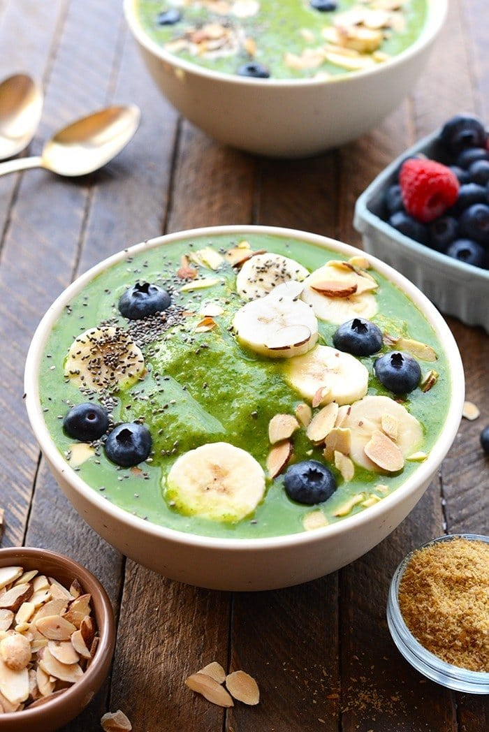 healthy green smoothie bowl topped with fruit and nuts and chia seeds