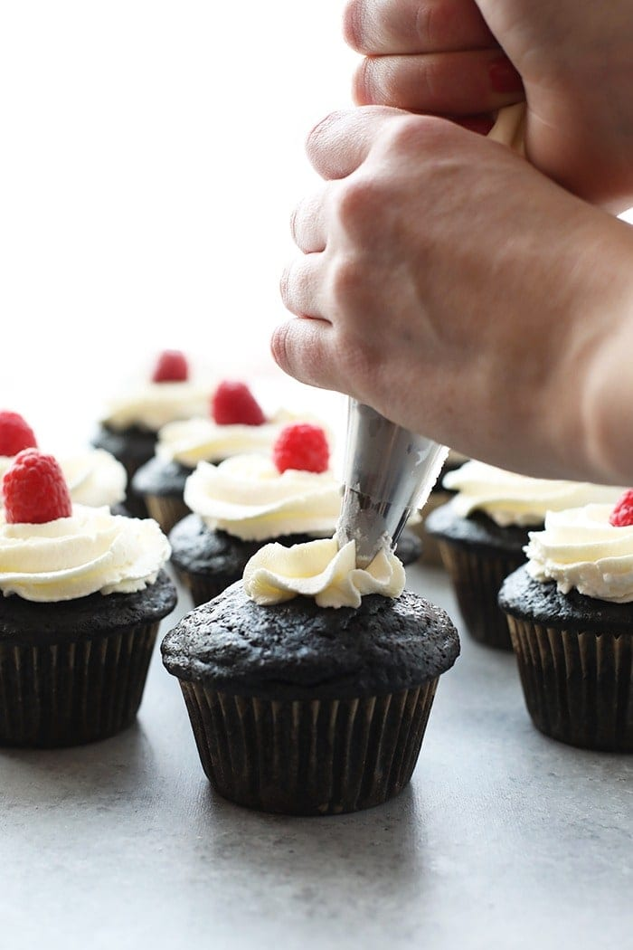 healthier chocolate cupcakes being piped with vanilla frosting and topped with a fresh raspberry