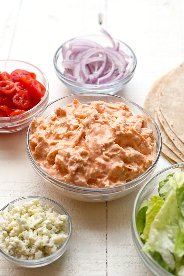 chicken wrap recipe ingredients in individual bowls including tomato, onion, lettuce and buffalo chicken