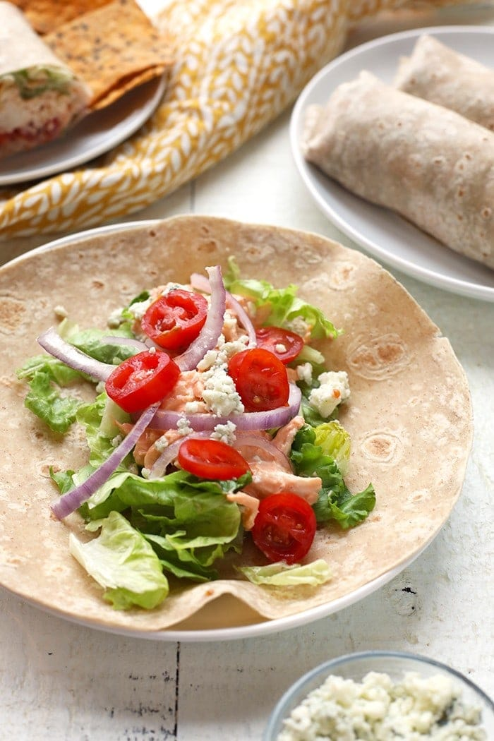 healthy chicken wrap ingredients on tortilla including tomatoes, onion and buffalo chicken