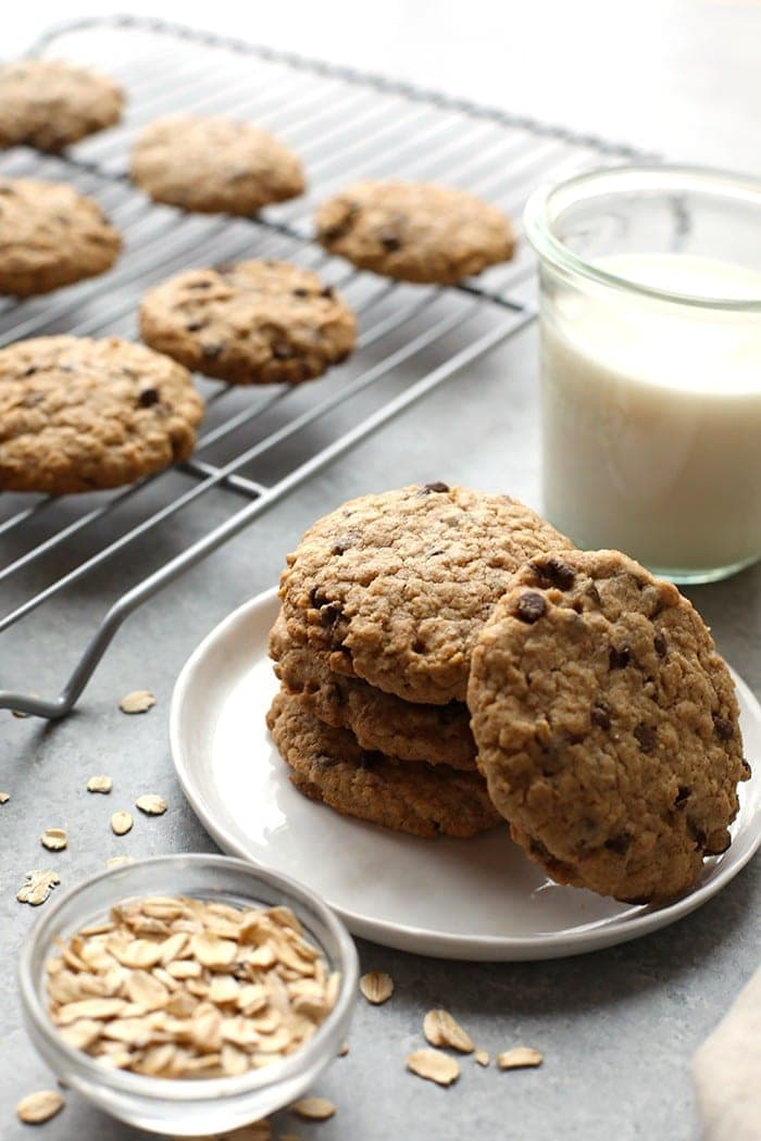 Healthy oatmeal cookies on a plate next to a glass of milk.