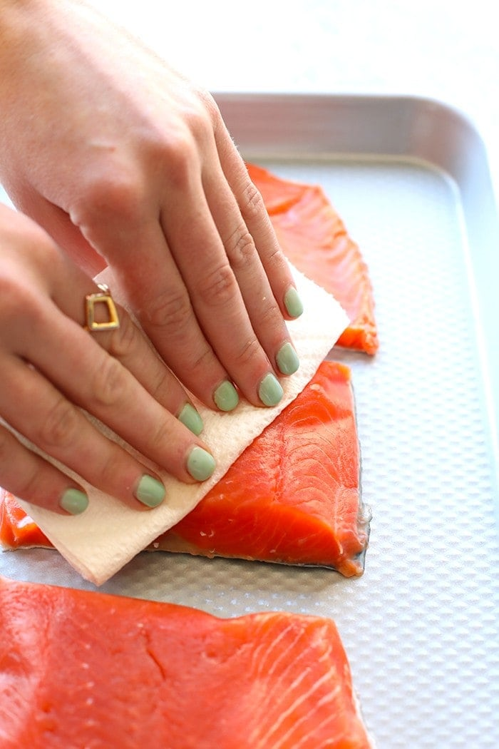 hands patting salmon fillets dry