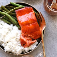 honey sriracha salmon on plate with rice and green beans and fork