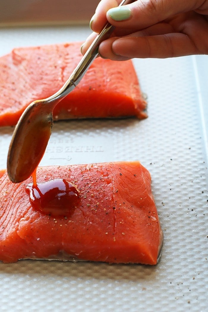honey sriracha sauce being poured over salmon