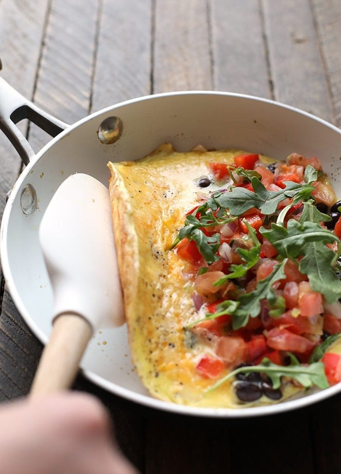veggie omelette being folded over in skillet