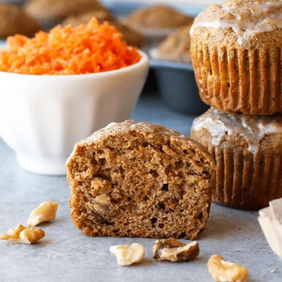 half of a healthy carrot muffin with bowl of shredded carrots in background