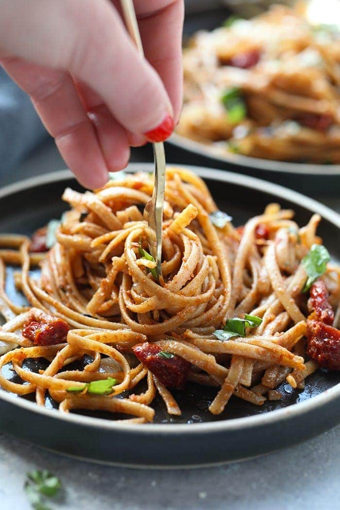 sun dried tomato pasta with whole wheat pasta twirled on fork