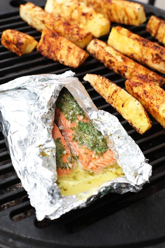Salmon in a foil on the grill with pineapple next to it